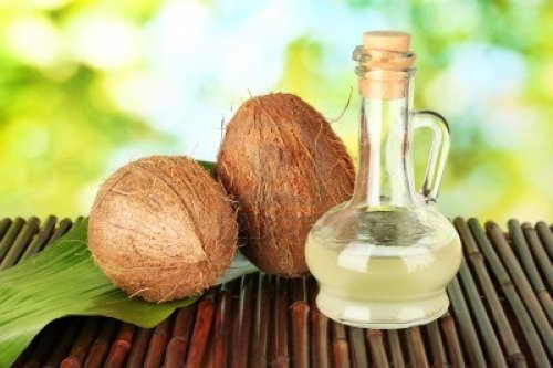 15283256-decanter-with-coconut-oil-and-coconuts-on-green-background1