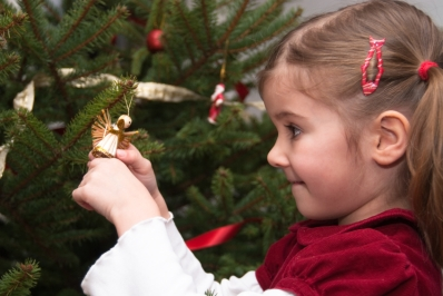 Young_girl_decorating_a_Christams_tree